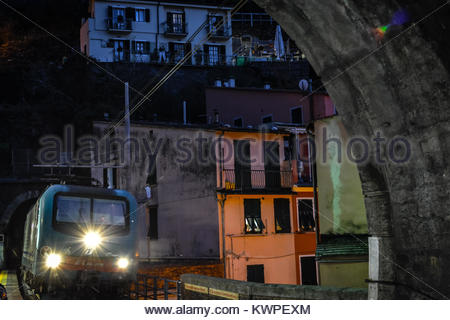 A night train's headlights shine as it enters a tunnel in the evening at Vernazza Italy, on the Cinque Terre coast - Stock Photo