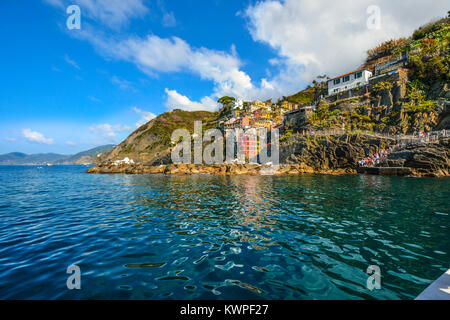 The colorful hillside village of Riomaggiore, Cinque Terre Italy, taken from the blue sea off the coast, with tourists - Stock Photo