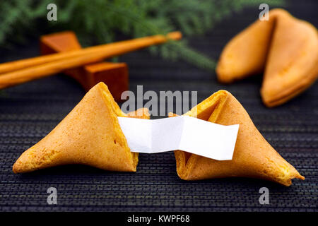 Fortune cookie with blank paper strip, another cookie and chopsticks on black napkin background. - Stock Photo
