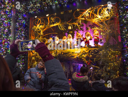 People take photos of 'The Seven Dwarfs'  in the Christmas holday display windows at Lord & Taylor on 5th Avenue - Stock Photo