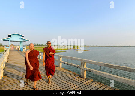 MANDALAY, MYANMAR - 3 JUN 2014: Two buddhist monks walk on the U-Bein teakwood bridge at sunrise, in Mandalay, Myanmar. - Stock Photo