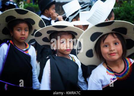Galapagos Islands children in traditional costume taking part in a street carnival, Puerto Ayora, Santa Cruz island, - Stock Photo