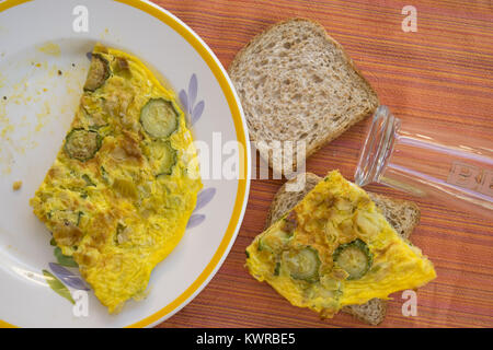 making a sandwich filled with zucchini omelette - Stock Photo