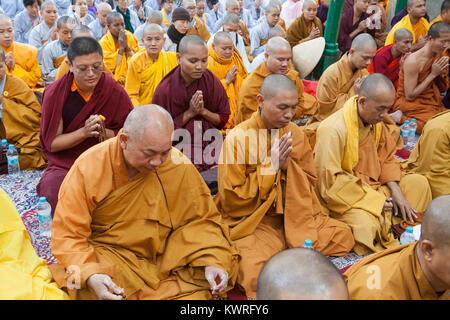 Monks praying at the foot of the Bodhi tree (where the Buddha is said to have gained enlightenment) at the Mahabodhi - Stock Photo