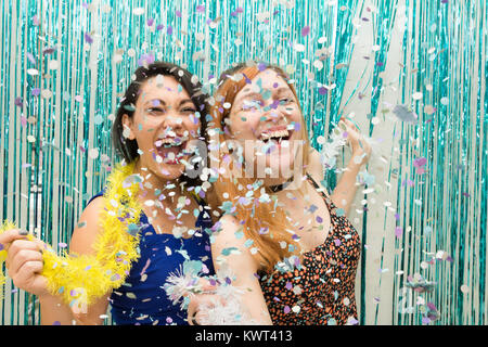 Two women, one Caucasian and one oriental, are celebrating Carnaval in Brazil. Much joy with the rain of confetti. - Stock Photo