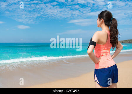 back view photo of pretty elegant female runner woman going to beach workout and looking at sea relaxing enjoying - Stock Photo