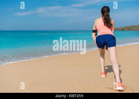 elegant attractive woman stretching legs making warm up ready running on beach to workout fitness during summer - Stock Photo
