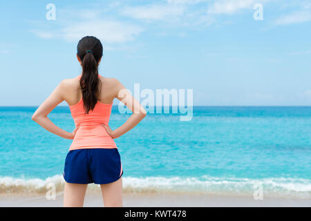 back view photo of pretty elegant woman runner finished training standing on beach relaxing and face to beautiful - Stock Photo
