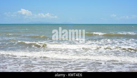 Small waves rolling in to a beach with blue skies, Bagal Beach near Townsville, Queensland, Australia - Stock Photo