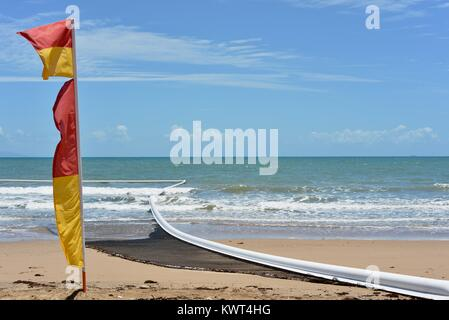 Red and yellow surf lifesaving flag with jellyfish nets in the background, Bagal Beach near Townsville, Queensland, - Stock Photo