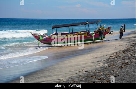 Lombok, Indonesia - Apr 16, 2016. Fishermen with a boat on sand beach of Lombok Island, Indonesia. Lombok is an - Stock Photo