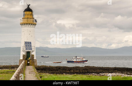 Tobermory, Scotland, UK - June 21, 2014: Boats in the Sound of Mull pass Rubha nan Gall lighthouse on the Hebridean - Stock Photo