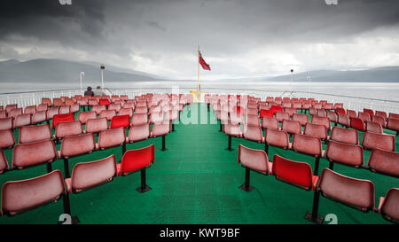 A couple sit alone in the rain on the open deck of the CalMac ferry from the Isle of Mull to Oban in Scotland's - Stock Photo