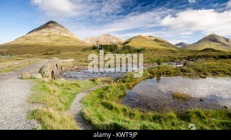 Old stone arch bridge over a mountain river at Sligachan on the Isle of Skye in the Highlands of Scotland, with - Stock Photo