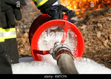 The fireman's hand holds a fire hose to extinguish a fire.Extinguish the fire. Fire hose - Stock Photo