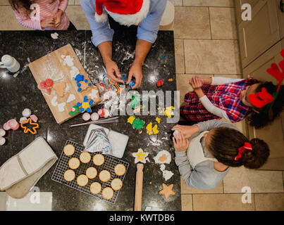 Aerial view of a father making christmas biscuits with his three daughters in the kitchen of their home. They are - Stock Photo
