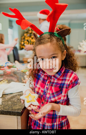 Proud little girl is posing for the camera with a christmas biscuit which she has made with her family at home.