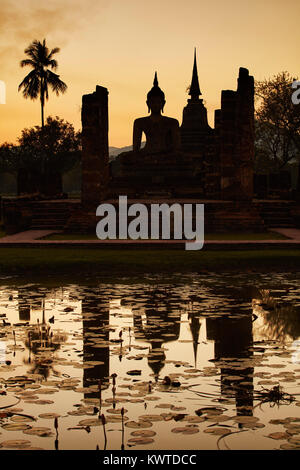 Wat Mahathat reflected in a lake, Sukhothai, UNESCO World Heritage Site, Thailand