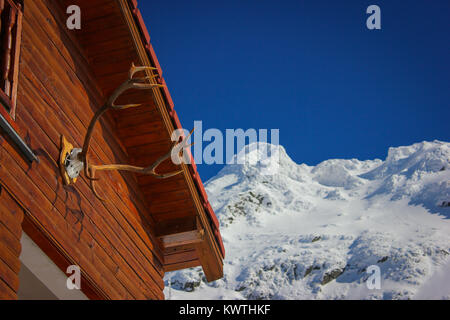 Alpine winter landscape with deer horns hunting trophy on a cabin at Balea Lake and Fagaras Mountains covered with - Stock Photo