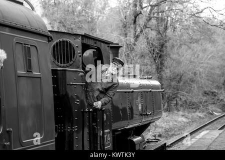 Black & white close up of vintage UK steam locomotive 7714 on railway line with engine driver on footplate leaning - Stock Photo