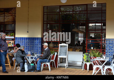 Senior couple seated at an outdoor table of a restaurant in the Mercado dos Lavradores, Funchal, Madeira, Portugal. - Stock Photo