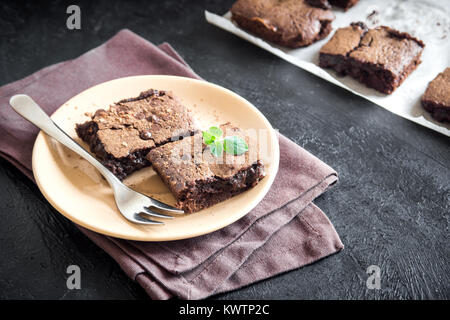 Double Chocolate Brownies. Homemade chocolate fudge brownies with chocolate chips and cocoa powder on black table. - Stock Photo