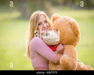 Teen girl and teddy-bear selective focus - Stock Photo