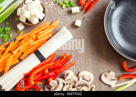 Vegetarian vegan asian food ingredients for stir fry with tofu, noodles, mushrooms and vegetables over wooden background - Stock Photo