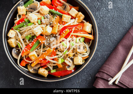 Stir fry with udon noodles, tofu, mushrooms and vegetables. Asian vegan vegetarian food, meal, stir fry in wok over - Stock Photo