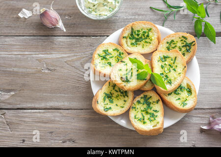 Toasted bread with garlic and herbs with ingredients over wooden background, copy space. - Stock Photo