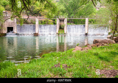 Concrete sluice with its reflection on water surface of Llobregat river in Catalonia, Spain - Stock Photo