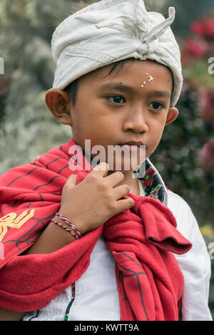 Young boy with wet rice grains on his forehead, Pura Besakih Temple, Mount Agung, Bali, Indonesia - Stock Photo