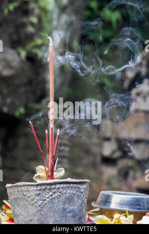 Burning incense, ruined Buddhist temple, Goa Gajah, Ubud, Bali, Indonesia - Stock Photo