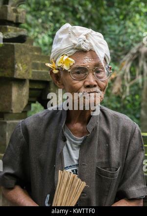 Elderly temple attendant in a light rain, Goa Gajah temple, Ubud, Bali, Indonesia - Stock Photo