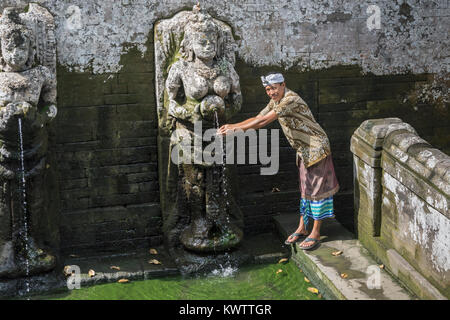 Balinese man in traditional dress ritually washing his hands at Goa Gajah bathing temple, Ubud, Bali, Indonesia - Stock Photo