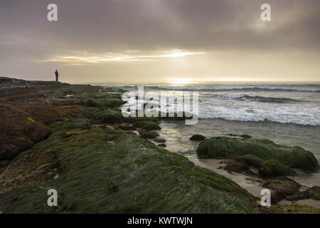 Distant Isolated Person enjoying Dramatic Sunset Sky over Pacific Ocean at Windansea Beach south of La Jolla California - Stock Photo