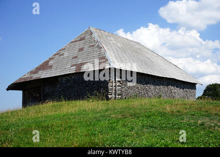 Wooden shed with firewood near the wall on the green hill in Swiss Alps, Switzerland - Stock Photo