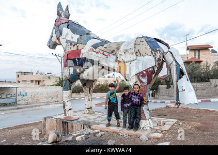 Jenin, Palestine, November 18, 2010: Palestinian children are standing in front of a horse built by German artist - Stock Photo