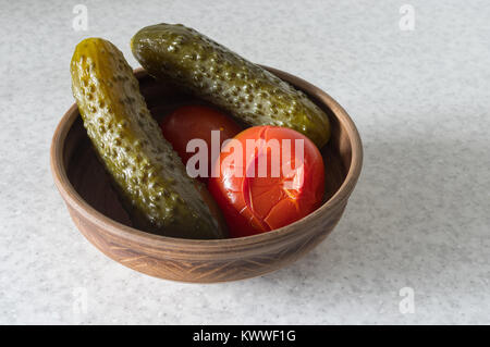 Ukrainian traditional appetizer - sour cucumbers and tomatoes in earthenware - Stock Photo