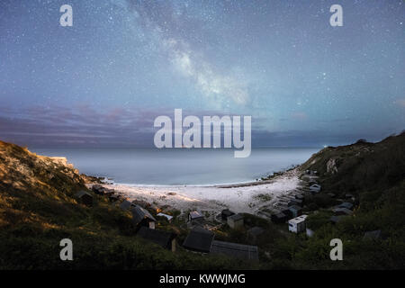 Church Ope Cove and its beach huts under the night sky and Milky Way on the Isle of Portland Dorset - Stock Photo