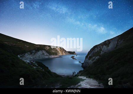 The Milky Way over St Oswald's Bay at Durdle Door on the Dorset Jurassic Coast - Stock Photo