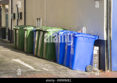 Row of blue and green wheelie bins outside a whitewashed building - Stock Photo
