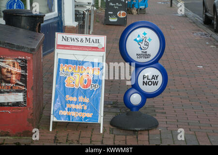 Signs on the pavement outside a newsagents shop advertising the national lottery and newspapers - Stock Photo