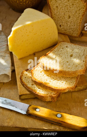 Loaf of Sourdough Bread Sliced on Wood Cutting Board Chunk of Cheese Knife Linen Towel. Golden Sunlight Flecks Rustic - Stock Photo