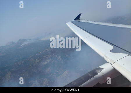 Aerial view from a plane to its wing and the land bellow - Stock Photo