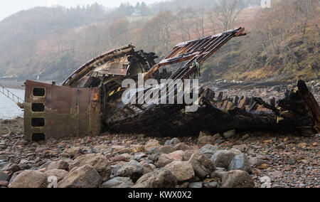 An old decaying fishing boat from yesteryear lies on the shoreline at Diabaig, Torridon in the Scottish Highlands - Stock Photo