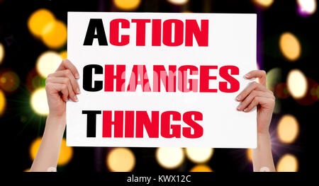 Action Changes Things. Female hands holding a placard with abstract lights bokeh background - Stock Photo