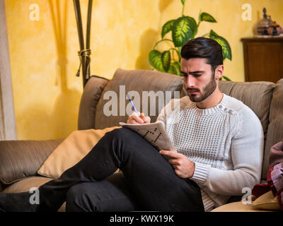 Young man sitting doing a crossword puzzle looking thoughtfully at a magazine, with his pencil to his mouth, as - Stock Photo