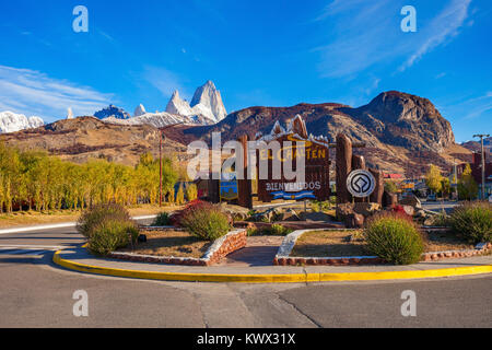 Road sign at the entrance of El Chalten village and Fitz Roy mountain on background. El Chalten located in Patagonia - Stock Photo