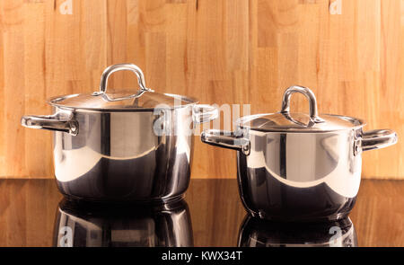 Traditional cooking pots placed on ceramic hob. Wooden background. Reflection, close up, details. - Stock Photo